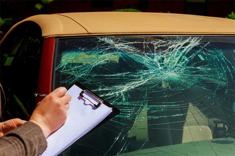 hail damage car insurance adjustor examine the car
